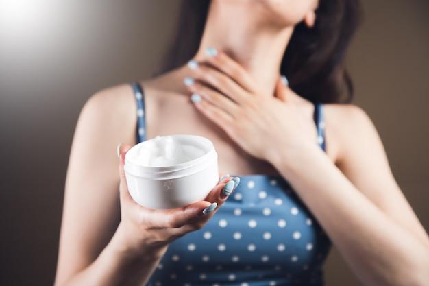 Vrouw smeert haar nek in met crème