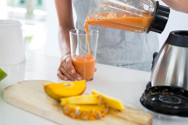 Vrouw smoothie gieten in glas aan balie in keuken