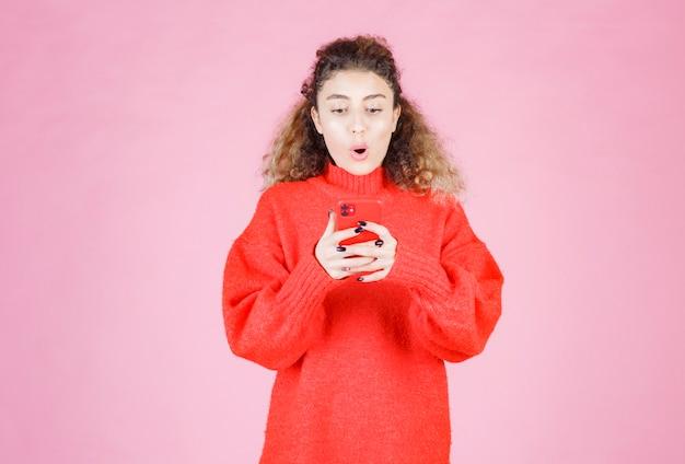 Vrouw sms't op haar nieuwe smartphone en voelt zich gelukkig.