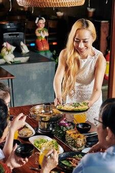 Vrouw snacks aan tafel te brengen
