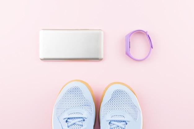 Vrouw sneakers, fitness tracker en smartphone op pastel roze achtergrond pastel
