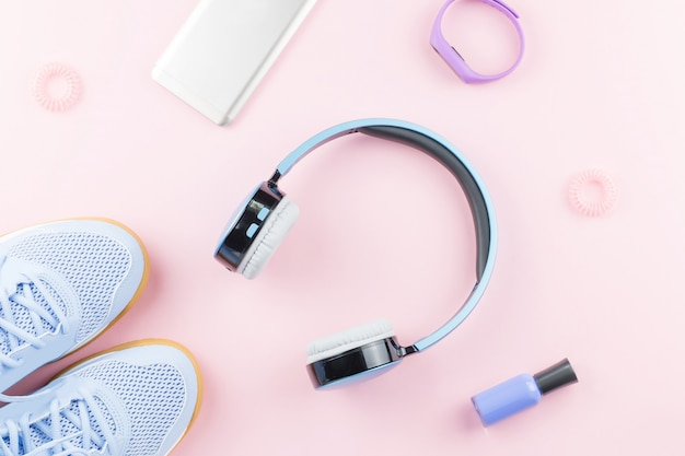 Vrouw sneakers, koptelefoon, fitness tracker en smartphone op pastel roze achtergrond. sport mode concept. plat liggen