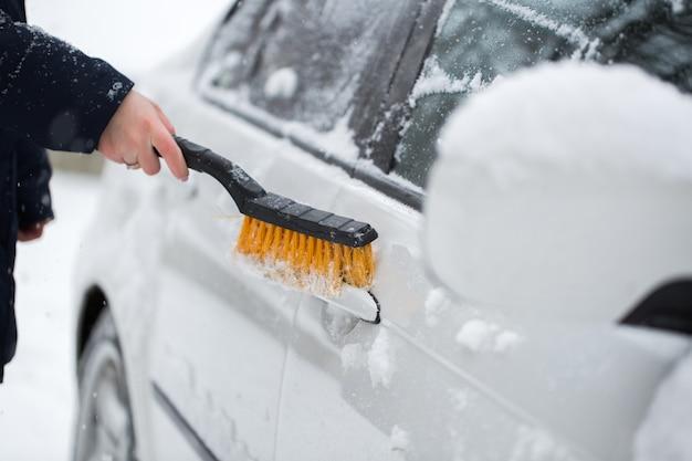 Vrouw sneeuw uit de auto schoonmaken in de winter. handgreep van de auto.