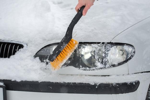 Vrouw sneeuw uit de auto schoonmaken in de winter. koplamp van de auto.