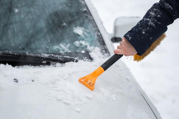 Vrouw sneeuw uit de auto schoonmaken in de winter