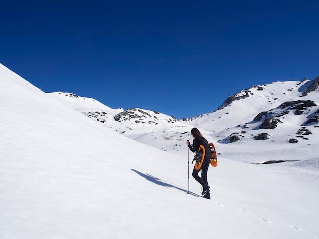 Vrouw sneeuwschoenwandelen in san isidro, león, spanje op een zonnige dag