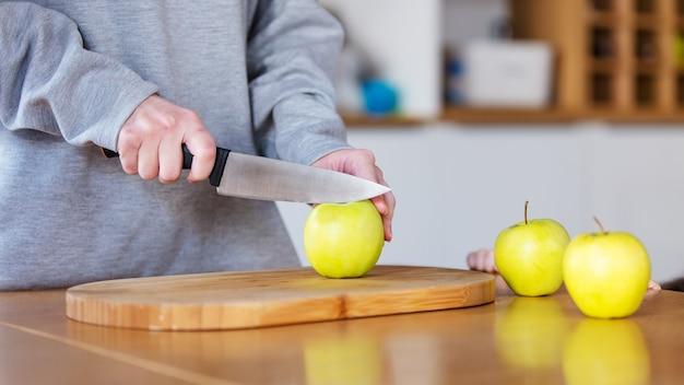 Vrouw snijd een appels op een bord met mes thuis keuken
