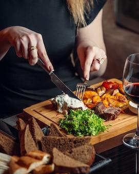 Vrouw snijden biefstuk met gesmolten cheddarkaas en romige saus