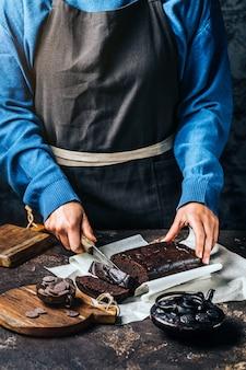 Vrouw snijden chocolade taart bijsnijden