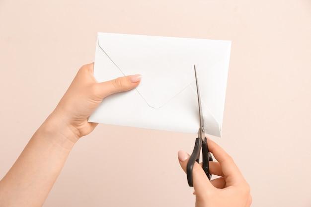 Vrouw snijden envelop op kleuroppervlak