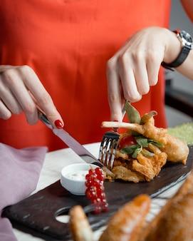 Vrouw snijden gebakken gegrilde kip met mes en vork
