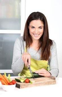 Vrouw snijden komkommer en in de keuken