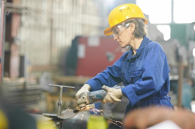 Vrouw snijden metaal in garage