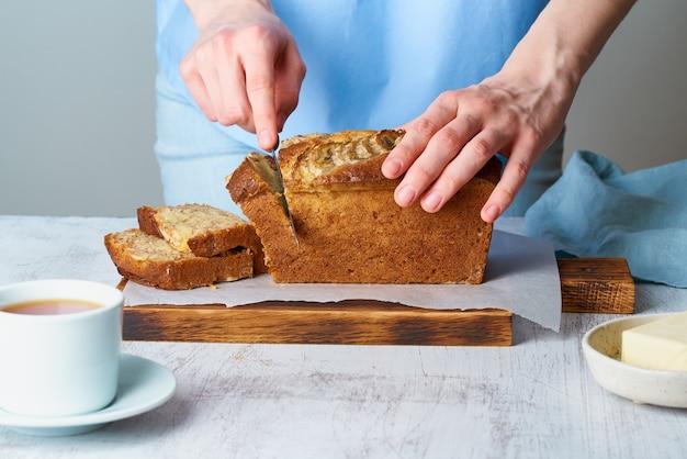 Vrouw snijdt bananenbrood op een houten bord. cake met banaan