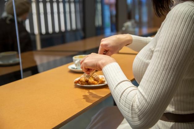 Vrouw snijdt croissant en drinkt koffie aan een tafel in een café. geen gezicht