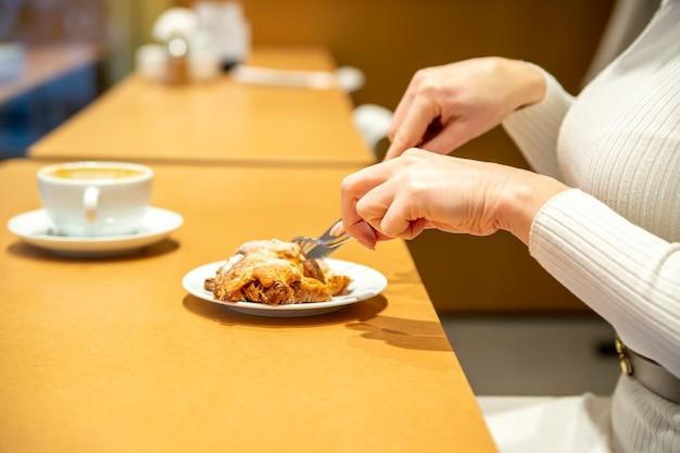 Vrouw snijdt croissant en drinkt koffie aan een tafel in een café