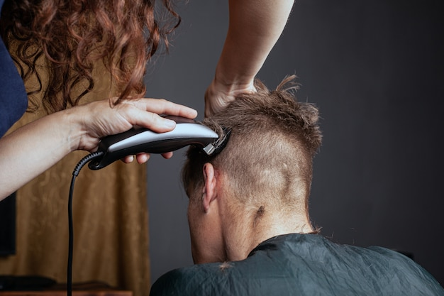 Vrouw snijdt een man met een trimmer in een kapper. stijlvol kapsel.