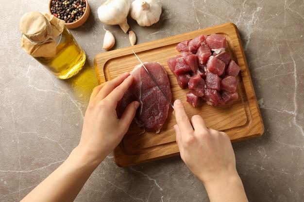 Vrouw snijdt rauw biefstuk vlees op een houten bord, bovenaanzicht