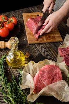 Vrouw snijdt rauw vlees om steaks te koken