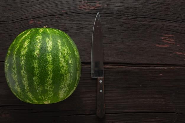 Vrouw snijdt rijpe watermeloen op een houten tafel