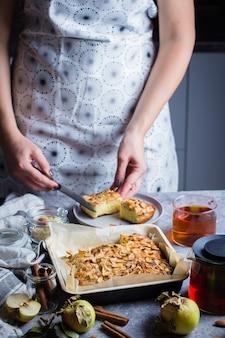 Vrouw snijdt stuk zelfgemaakte appeltaarten. norwegian biscuit pie op stenen betonnen tafel achtergrond