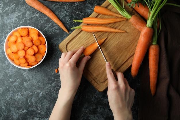 Vrouw snijdt wortelen op een houten bord op zwarte smokey achtergrond