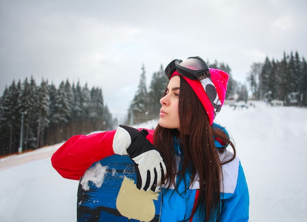 Vrouw snowboarder in de winter in skitoevlucht op achtergrond van pijnboombomen