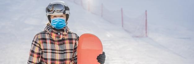 Vrouw snowboarder op een zonnige winterdag in een skigebied met een medisch masker tijdens covid-19