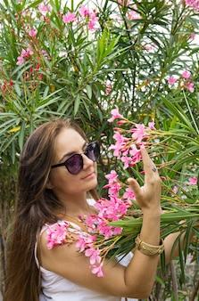 Vrouw snuffelt oleanderbloemen in de tuin
