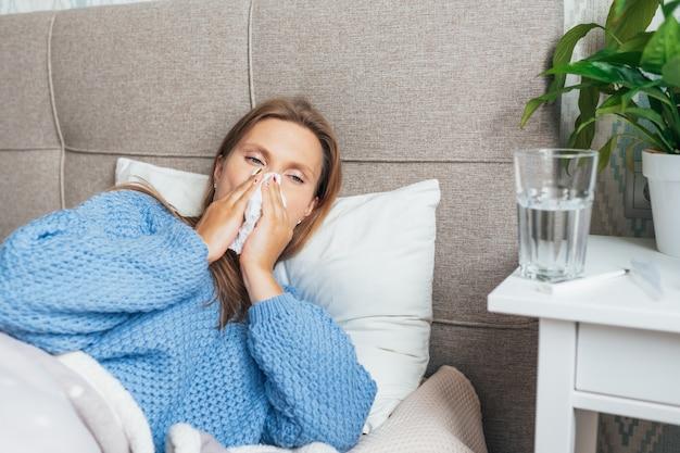 Vrouw snuit haar neus met een zakdoek van weefsel, met symptomen van verkoudheid of griep.