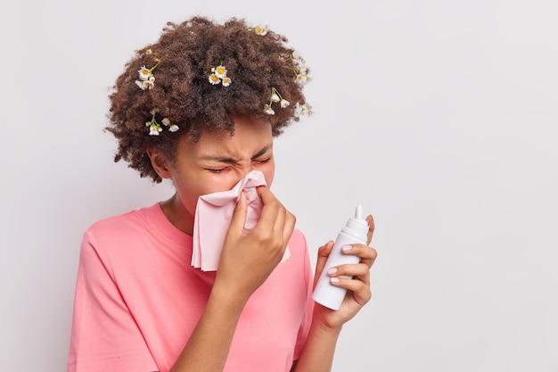 Vrouw snuit neus in tissue sprays aerosol heeft allergische reactie draagt casual roze t-shirt geïsoleerd op wit