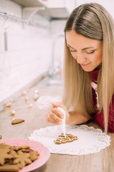 Vrouw soft focus trekt met glazuur een kerstboom peperkoek cookie in een rode trui op een wit servet. kerstvoorbereidingen. verticale foto