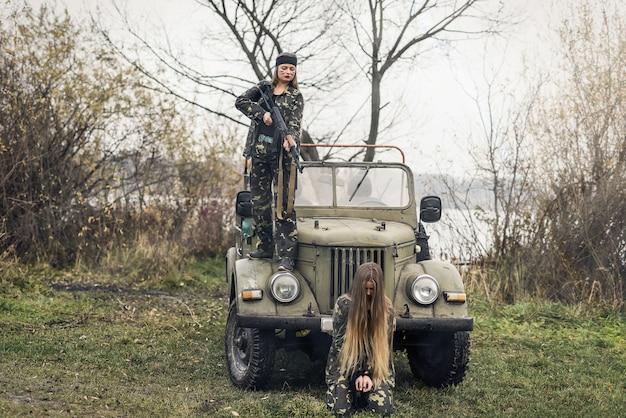 Vrouw soldaat en haar gijzelaar tegen militaire auto