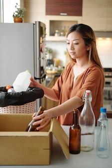 Vrouw sorteert glazen en plastic flessen