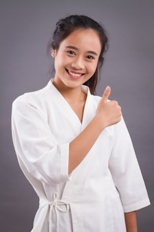 Vrouw spa therapeut duim omhoog. aziatische vrouw spa-therapeut