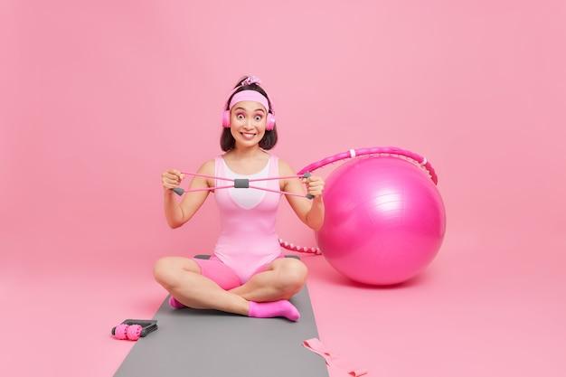 Vrouw spant expander traint armspieren zit gekruiste benen op fitnessmat heeft regelmatige training luistert muziek via koptelefoon geïsoleerd op roze