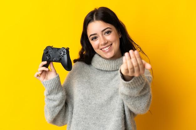 Vrouw speelt met een videogamecontroller geïsoleerd op geel en nodigt uit om met de hand te komen. blij dat je gekomen bent