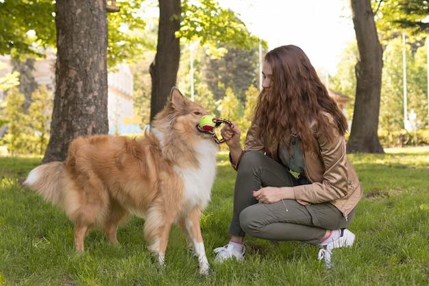 Vrouw speelt met haar hond in het park