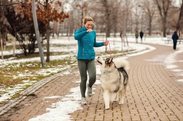 Vrouw speelt met haar hond tijdens het wandelen in het park op besneeuwde winterdag. huisdieren, sneeuw, vriendschap, weekendactiviteiten