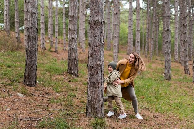 Vrouw speelt met haar zoon in het bos