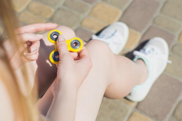 Vrouw speelt met handspinner zittend op een bankje buiten