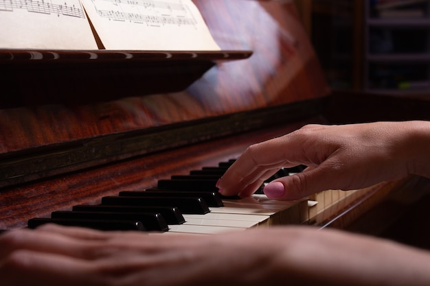 Vrouw speelt piano bladmuziek close-up