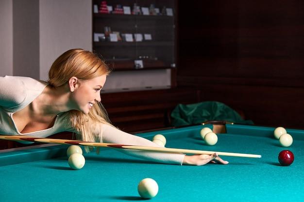 Vrouw speelt snooker, ze streeft ernaar om de snookerbal te schieten, hand in hand op de snookertafel. biljart