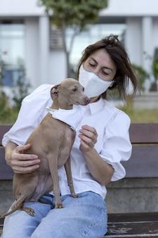 Vrouw spelen met hond, het dragen van een coronavirus beschermend masker
