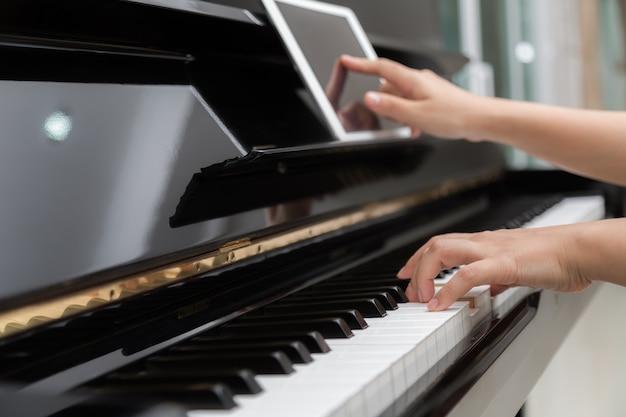 Vrouw spelen piano en met behulp van haar digitale tablet
