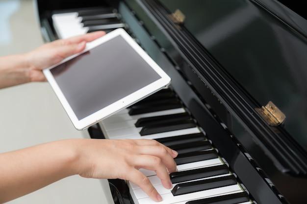 Vrouw spelen piano hand die een tablet