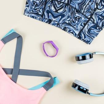 Vrouw sport kleding, sneakers, koptelefoon en fitness tracker op neutrale achtergrond. sport mode concept. plat liggen