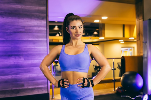 Vrouw sport oefeningen doen en poseren voor de camera in de sportschool