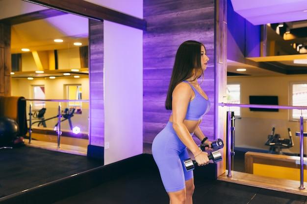 Vrouw sport oefeningen met halters in de sportschool, in een blauw sport-pak