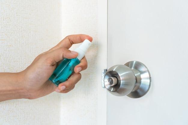 Vrouw spray alcohol aan deurknop voor bescherming tegen besmettelijke virussen, bacteriën en ziektekiemen, close-up